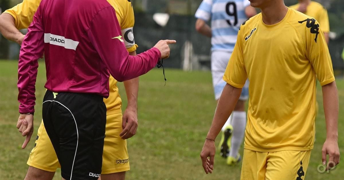 Arbitro in maglia fuxia e giocatore maglia gialla