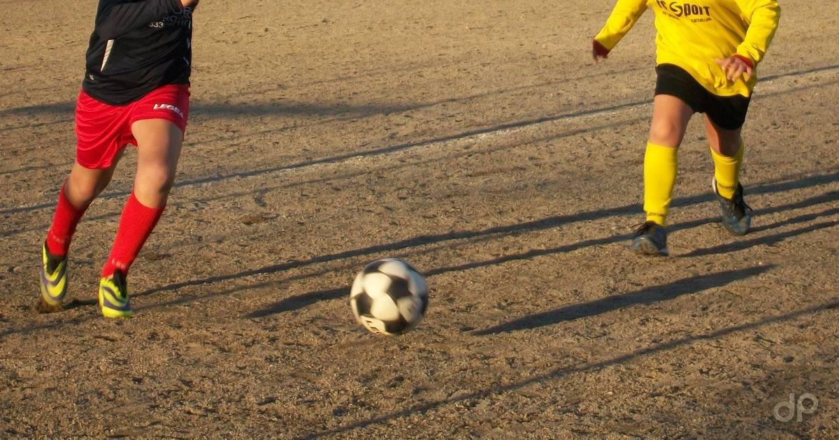 Giocatori dilettanti su campo da calcio in terra battuta