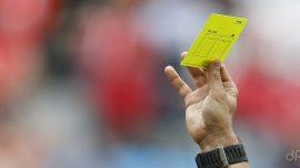 Arbitro alza cartellino giallo