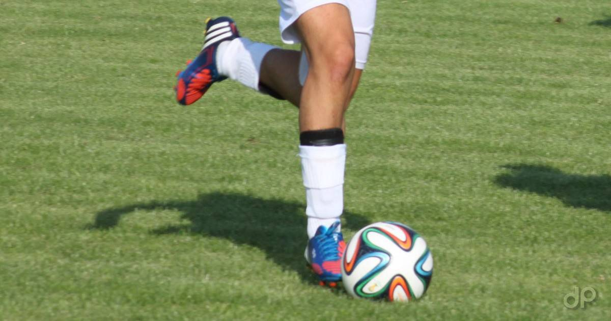 Particolare giocatore con pallone in calzettoni bianchi