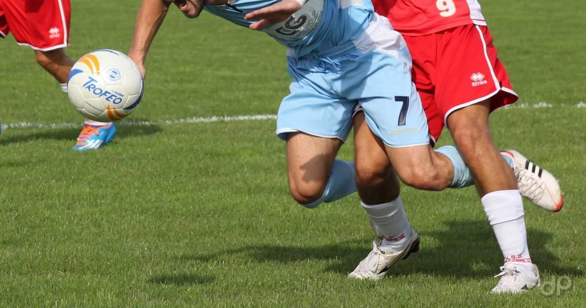 Giocatori calcio inseguono pallone
