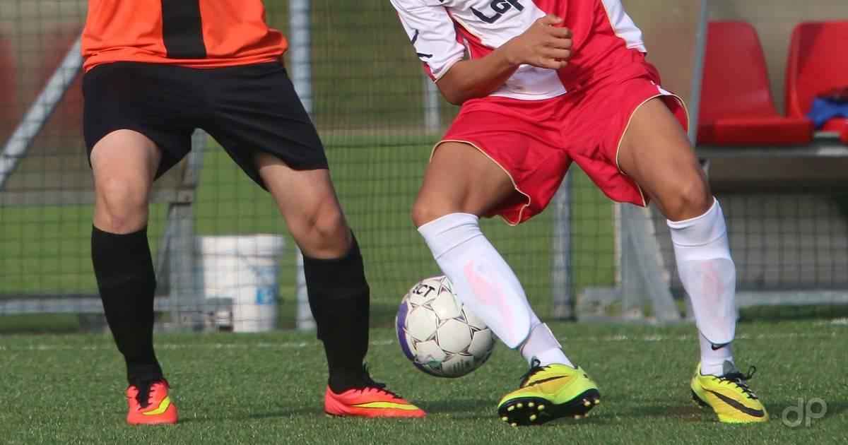 Giocatori in azione maglia arancione e maglia rossa