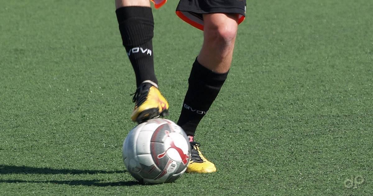 Dettaglio giocatore che ferma la palla coi piedi