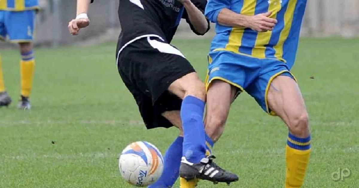 Giocatori dilettanti in azione in maglia nera e in maglia azzurra