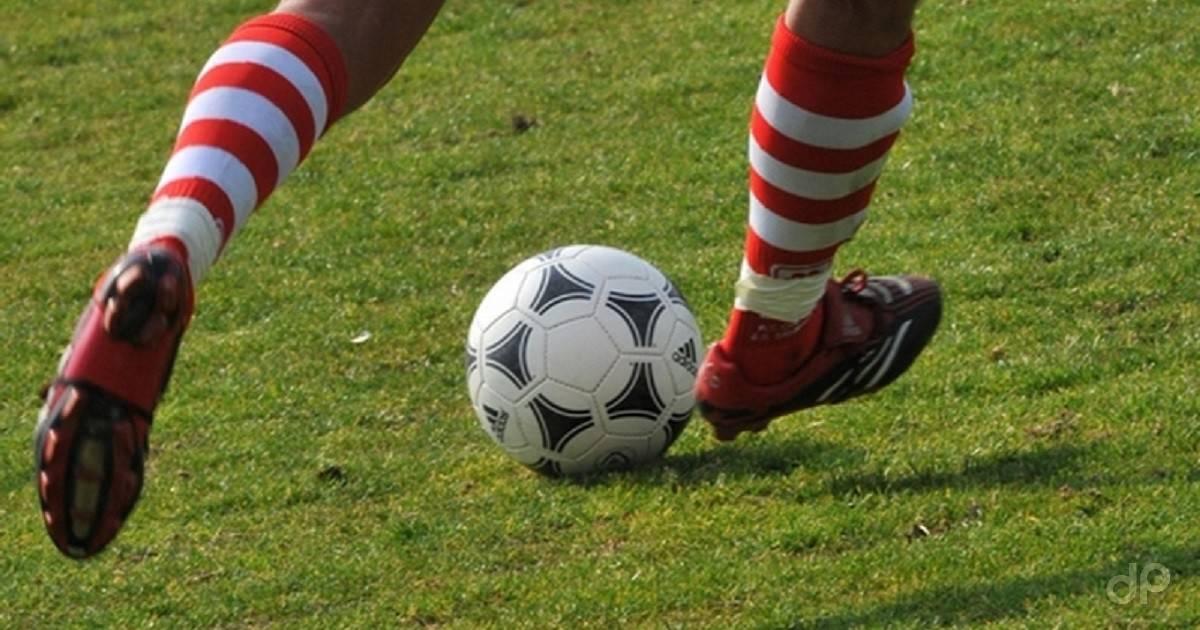 Giocatore in calze biancorosse con un pallone