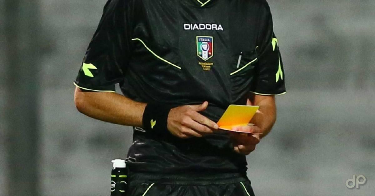 Arbitro maglia nera con cartellino in mano