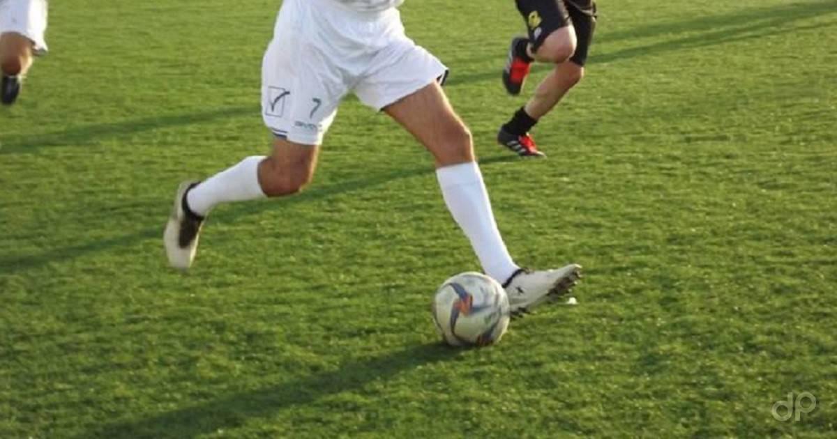 Dettaglio calciatore dillettante in corsa con pallone