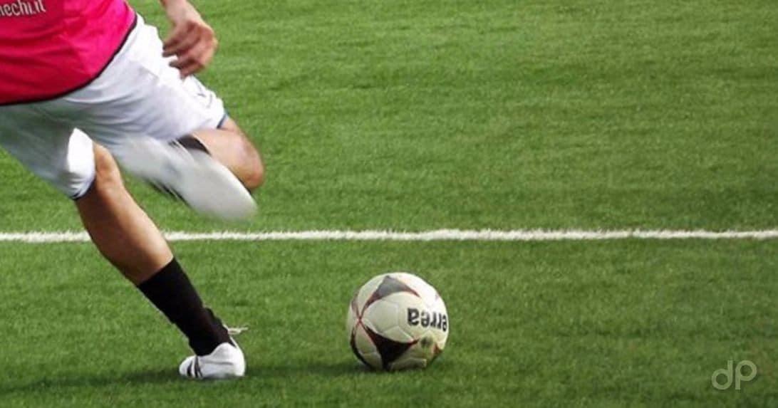 Giocatore in corsa con pallone maglia fuxia