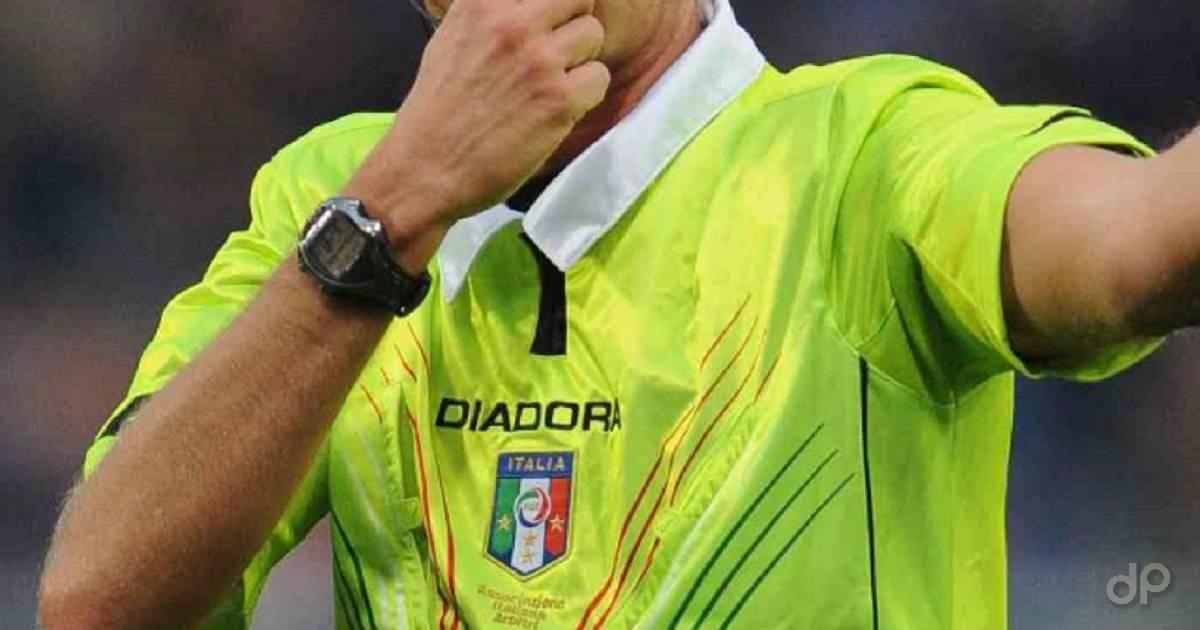 Arbitro in maglia gialla con fischietto
