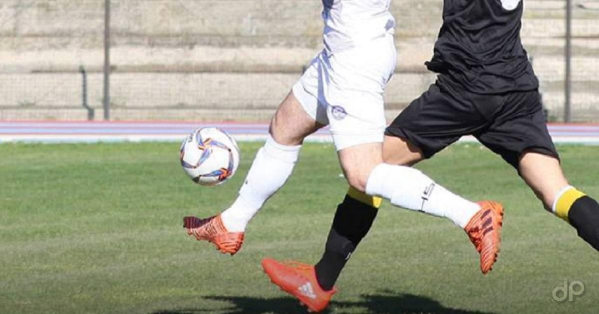 Calciatore con pallone pantaloni bianchi