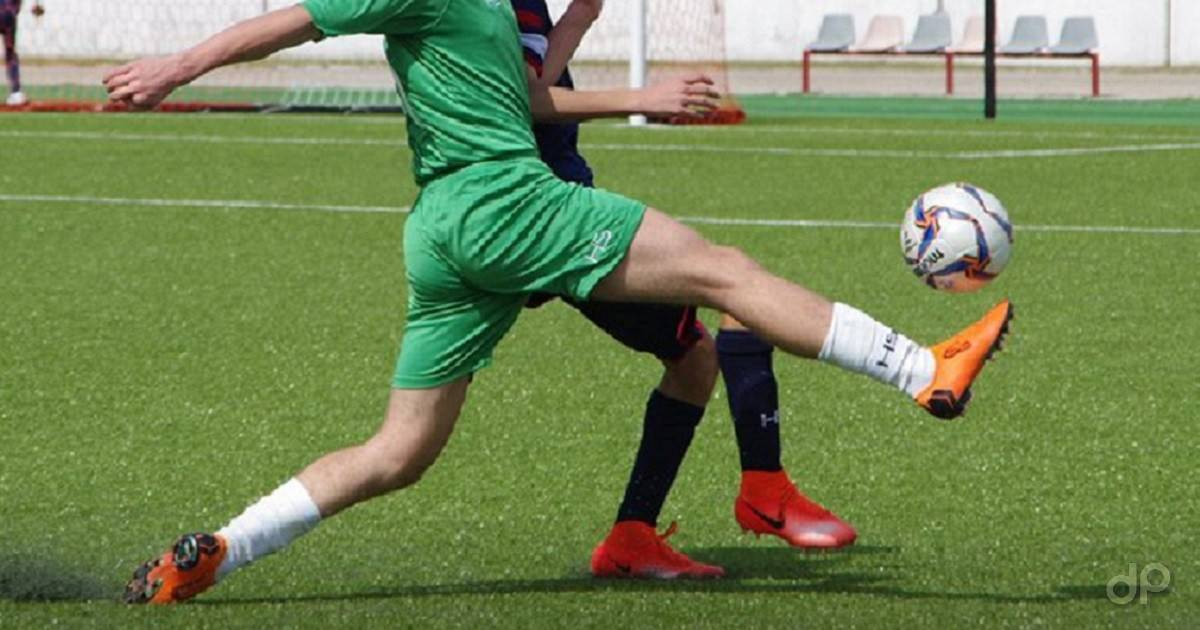 Calciatore con pallone pantaloni verdi