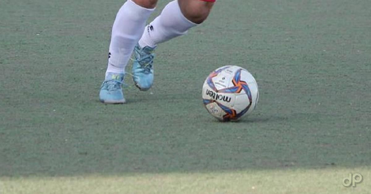 Giocatore con pallone scarpe azzurre