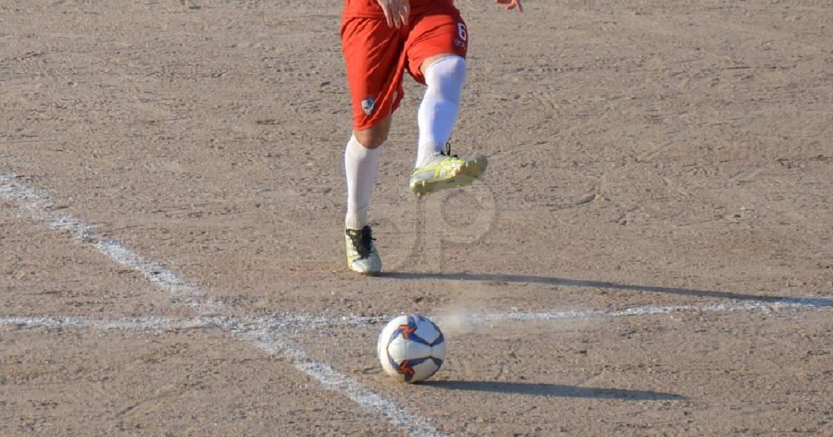 Giocatore con pallone su terra battuta in maglia rossa