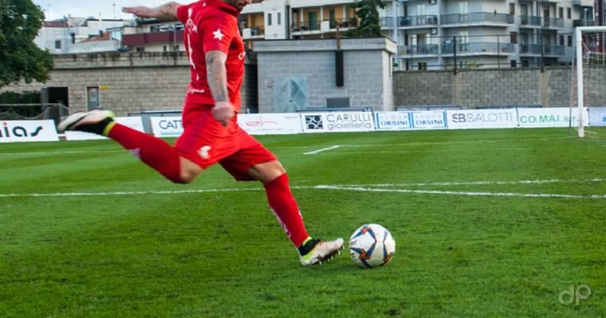 Giocatore pallone tiro maglia rossa