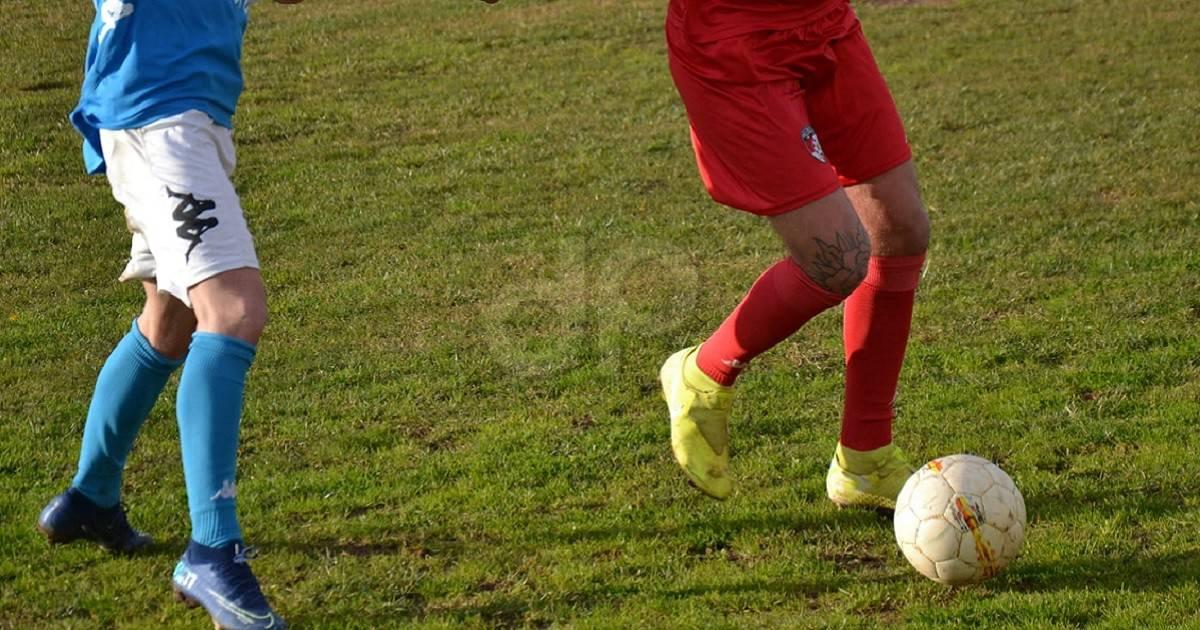 Calciatori calzettoni rossi e celesti con pallone bianco