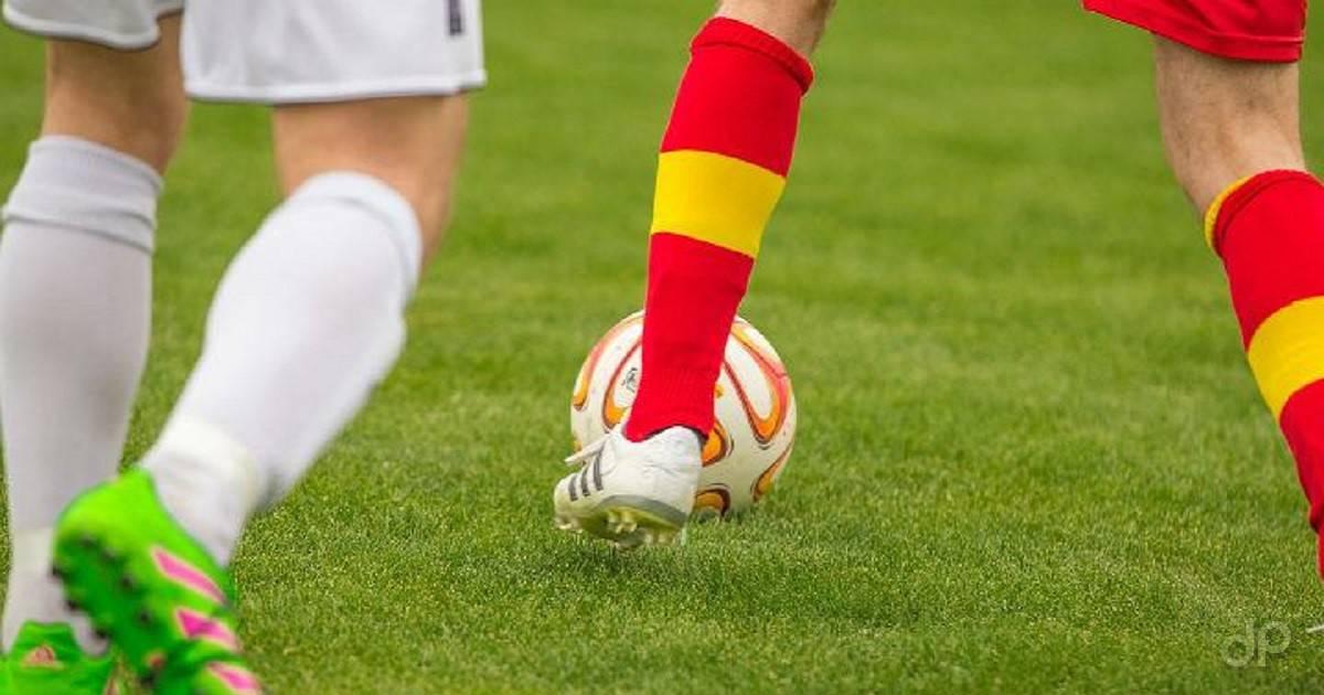 Pallone calcio e giocatori con calzettoni giallorossi e bianchi