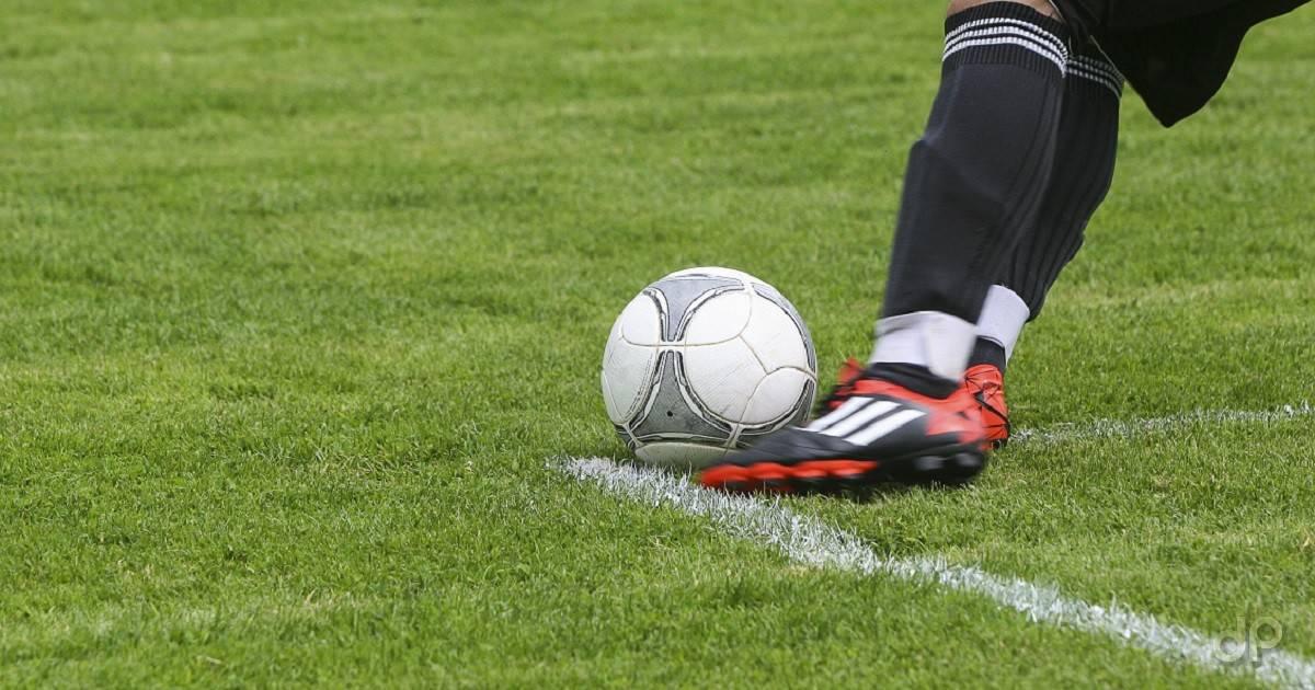 Pallone calcio e giocatore con calzettoni neri