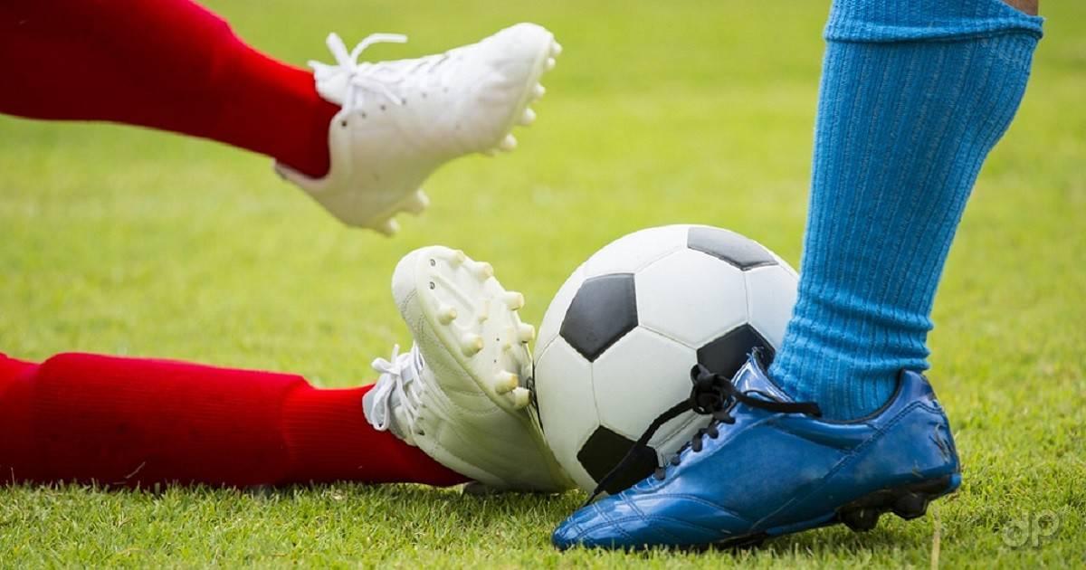 Pallone calcio e giocatori con calzettoni rossi e azzurri